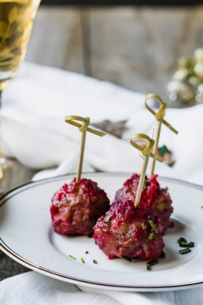 Three turkey meatballs on a white plate with toothpicks and green herb garnish