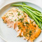A large piece of baked salmon with dill and green beans on a grey plate.