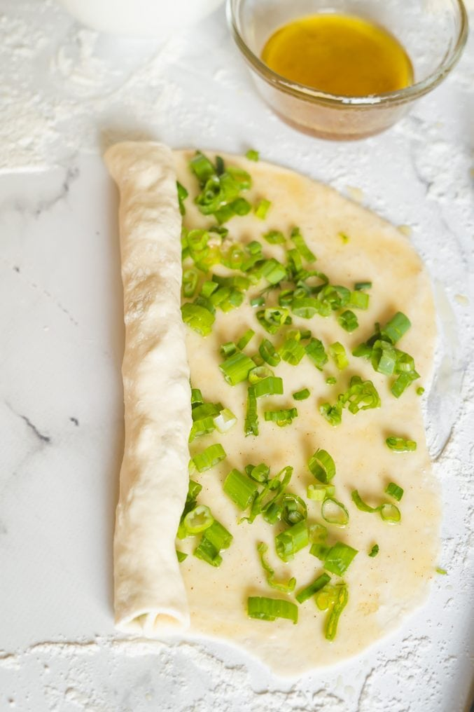 Scallion pancakes being rolled up into a long roll