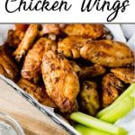 Pinterest pin showing a basket of spicy roasted chicken wings with some celery and dip