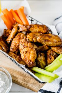 basket of spicy chicken wings with some carrot and celery sticks on a wood board