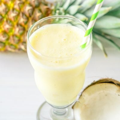 A smoothie with pineapple and coconut on a white table
