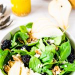 A bowl of winter salad with bosc pears, blackberries and walntuts