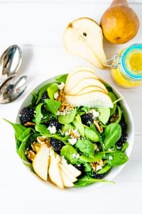 A white tablescape showing a bowl of spinach salad with pears, blackberries and walnuts