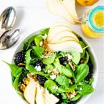 A white table with a bowl of winter salad made with spinach and a jar of Meyer lemon vinaigrette