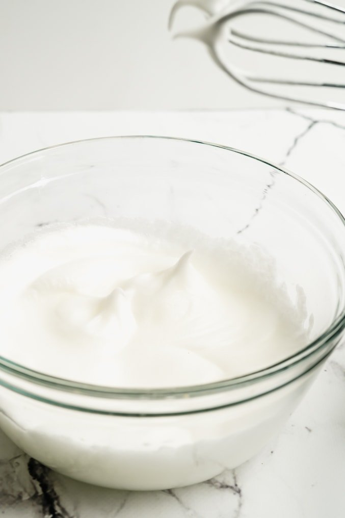 egg whites whipped to firm peaks in a glass bowl
