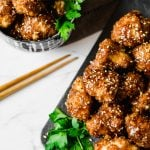 Air-fryer cauliflower bites tossed with Korean BBQ sauce on a platter and in a small bowl with some chopsticks