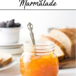 Pinterest pin showing orange preserves made in a small jar with a spoon on a breakfast table.