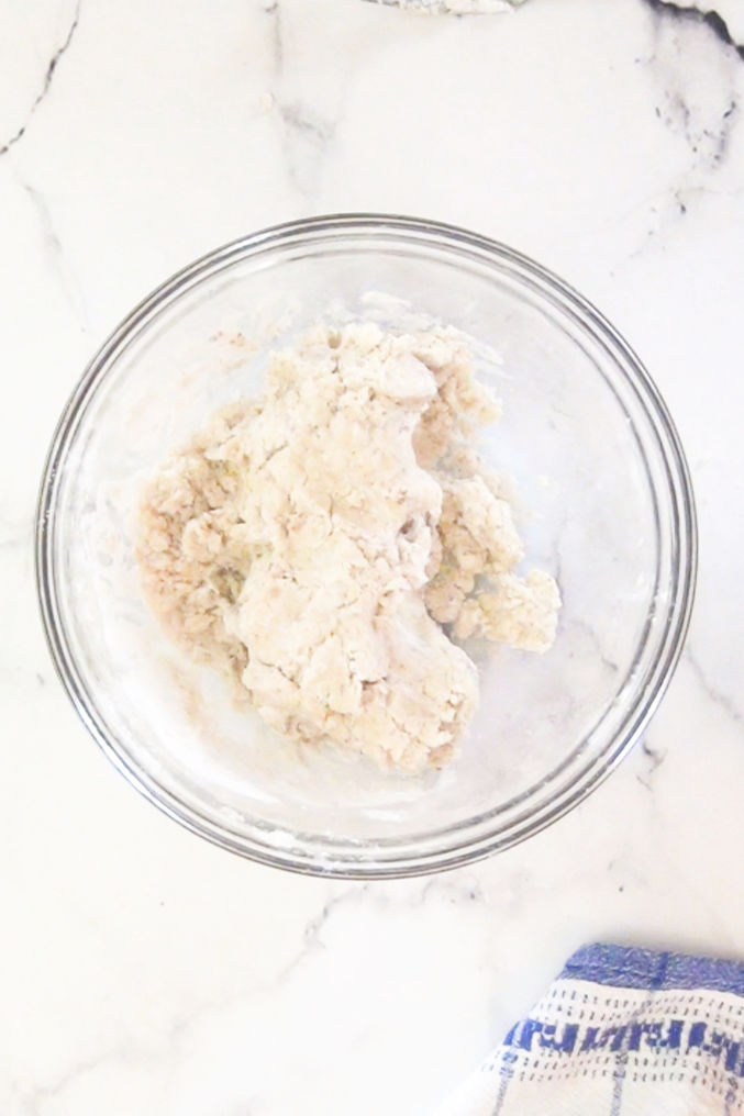 Bowl of vegan cookie recipe batter on a white marble table.