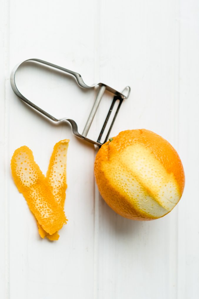 Naval orange on a white table beside a potato peeler being peeled for orange marmalade