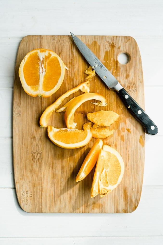 A cutting board with oranges being sectioned for marmalade