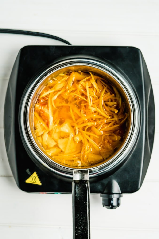 A pot of orange peel, orange flesh and sugar being boiled with water to make homemade marmalade