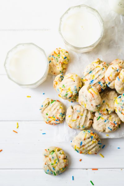 Overhead shot of a pile of funfetti cookies with two glasses of milk on a white wood table