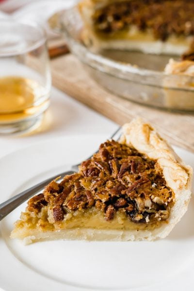 A slice of southern pecan pie on a white plate