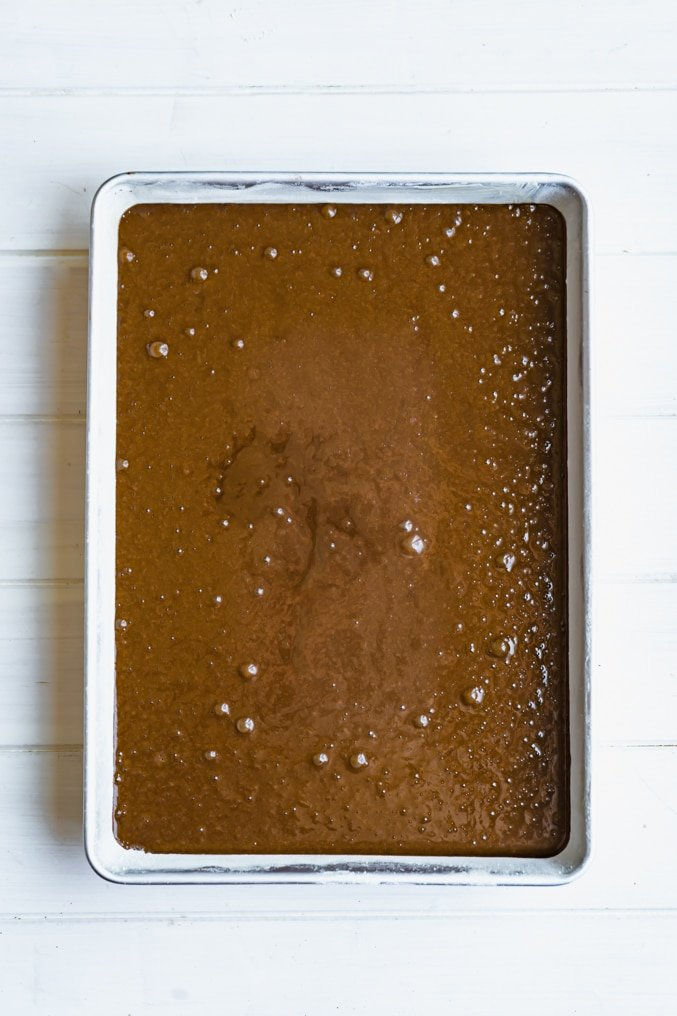 A raw chocolate sheet cake in a cake pan on a white table