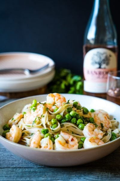 A bowl of spicy shrimp pasta with peas and fettuccine on a table with a bottle of Moscato