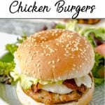 Pinterest pin showing a homemade chicken burger dressed with bacon, mayo and lettuce with a side salad.