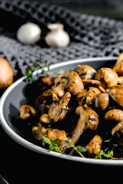 A plate of garlic mushrooms on a grey background decorated with sprigs of fresh thyme