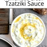 Pinterest pin showing a bowl of Greek tzatziki sauce on a slate plate near a plate of kebabs