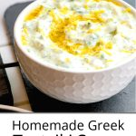 Pinterest pin of tzatziki sauce in a white bowl on a grey platter drizzled with olive oil