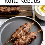 Pinterest pin showing a close up of two grilled kofta kebobs on grey plate with tzatziki nearby