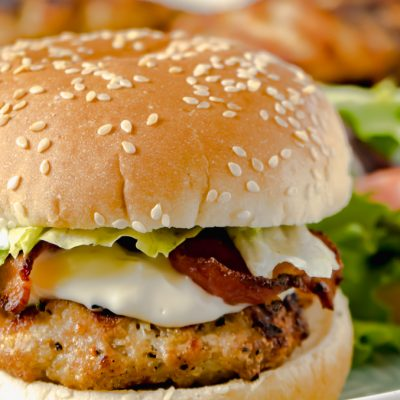 A close up of a chicken burger dressed with lettuce, bacon and mayo on a bun with more in the background