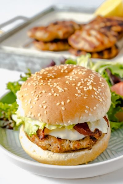 A BBQ Chicken Burger all dressed on a bun with a side salad and a tray of more burgers in the back.