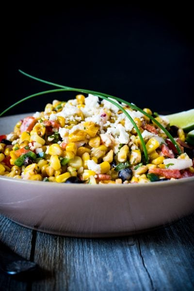 Mexican corn salad recipe in a bowl with chives on a black background