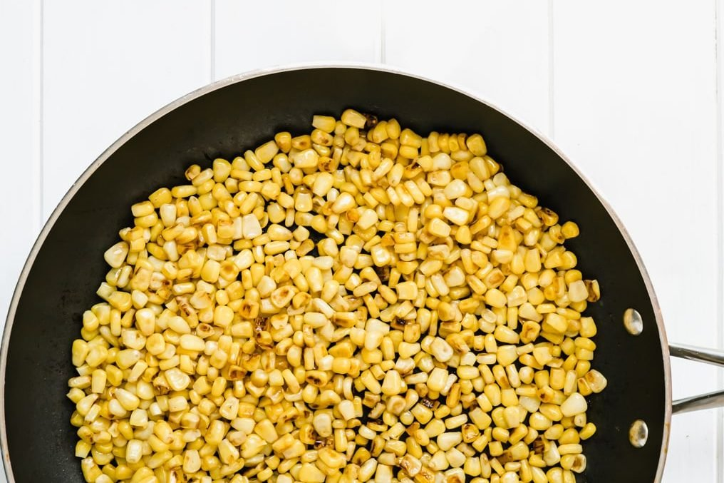 Corn being lightly browned in a pan