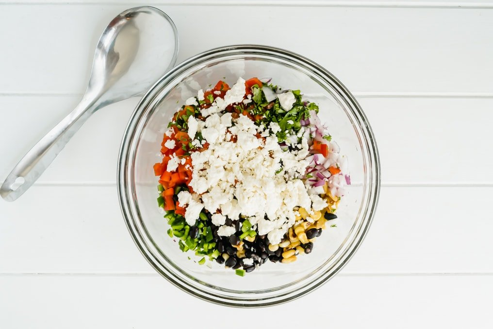 A bowl of salad with feta on top and a spoon nearby