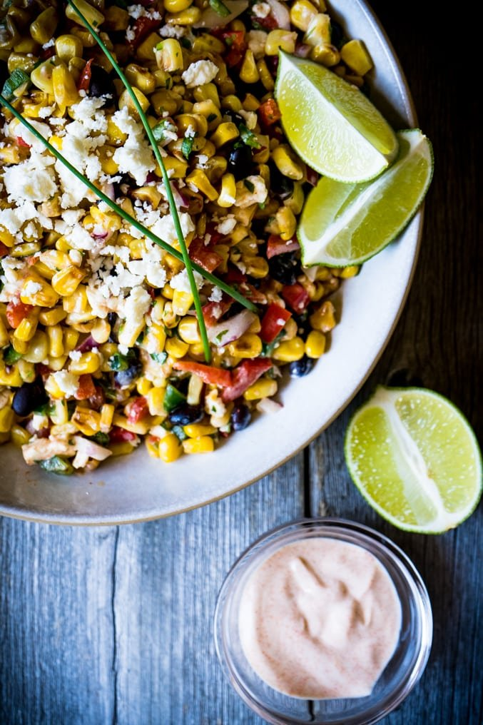 A corn salad with black beans with limes on a wood table with dressing beside