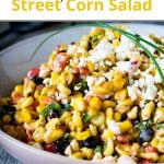 Pinterest pin showing close up of a corn salad in a bowl on grey table.