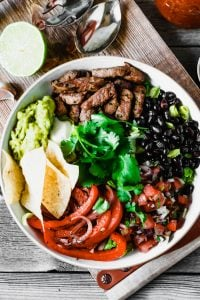 A Steak Burrito Bowl Salad recipe in a large bowl with tortilla chips