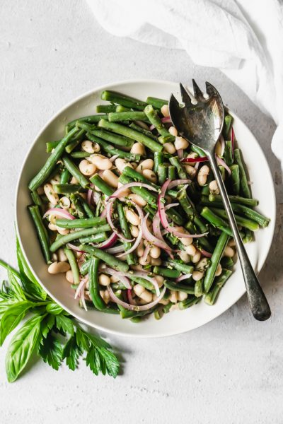 Overhead shot of a bowl of white and green bean salad with a silver serving spoon on a white table