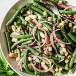 A bowl of white bean salad made with green beans and red onions