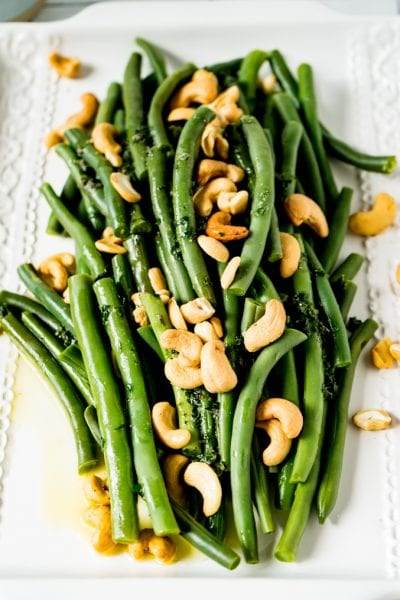 A white platter of green beans and cashews smothered in butter