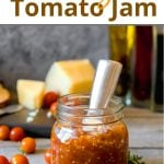 Pinterest pin for a recipe for tomato jam showing a filled glass jar and spoon on a table with cheese and tomatoes
