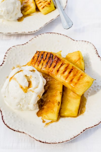 Grilled pineapple slices on a white plate with ice cream and a rum glaze