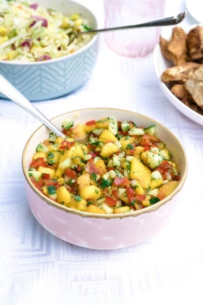 A bowl of peach salsa made with cucumbers on a white table