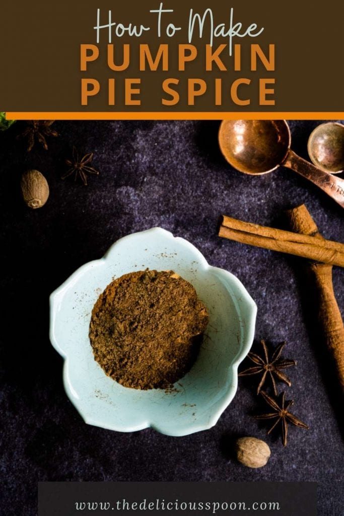 A pinterest pin showing a small bowl filled with a homemade pumpkin spice recipe on a dark table with cinnamon sticks and nutmeg