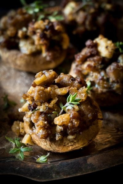 Keto stuffed mushrooms on a silver platter decorated with fresh thyme.