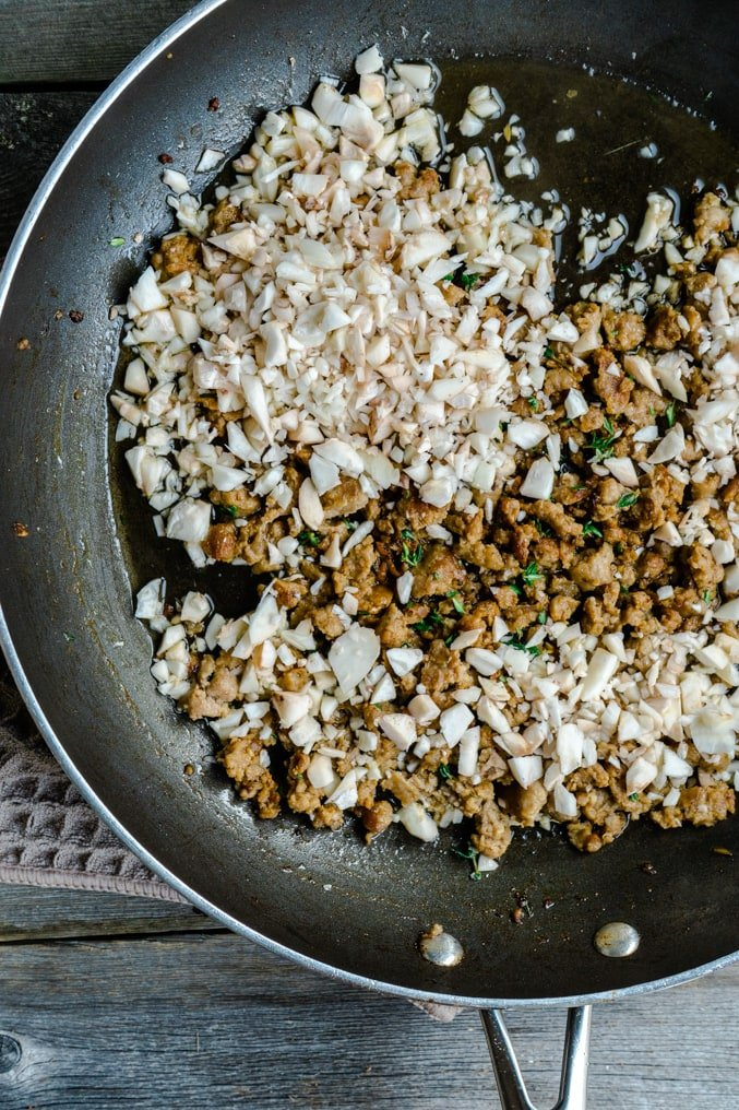 Crumbled sausage and diced mushroom stems in a pan