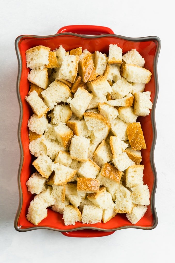 A red casserole dish filled with cubed bread