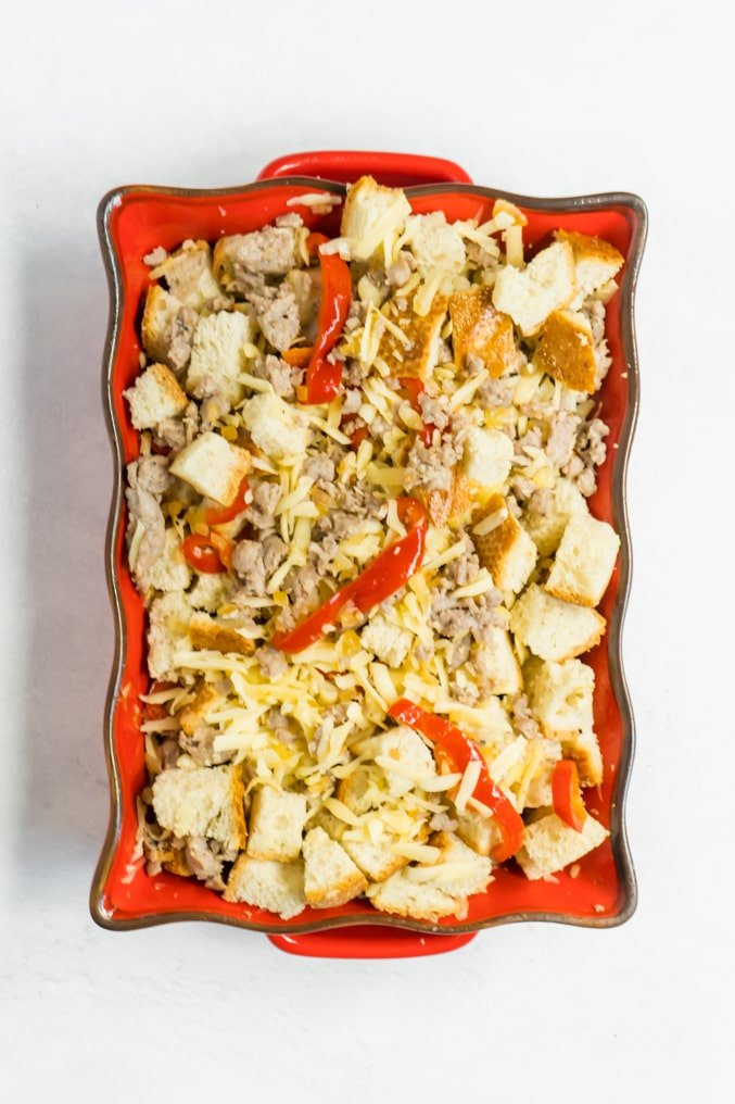 A casserole dish filled with bread cubes, cheese, sausage, red peppers and onions.