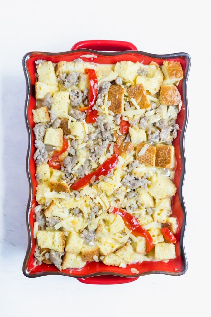An uncooked sausage and pepper breakfast strata recipe in a red casserole dish.