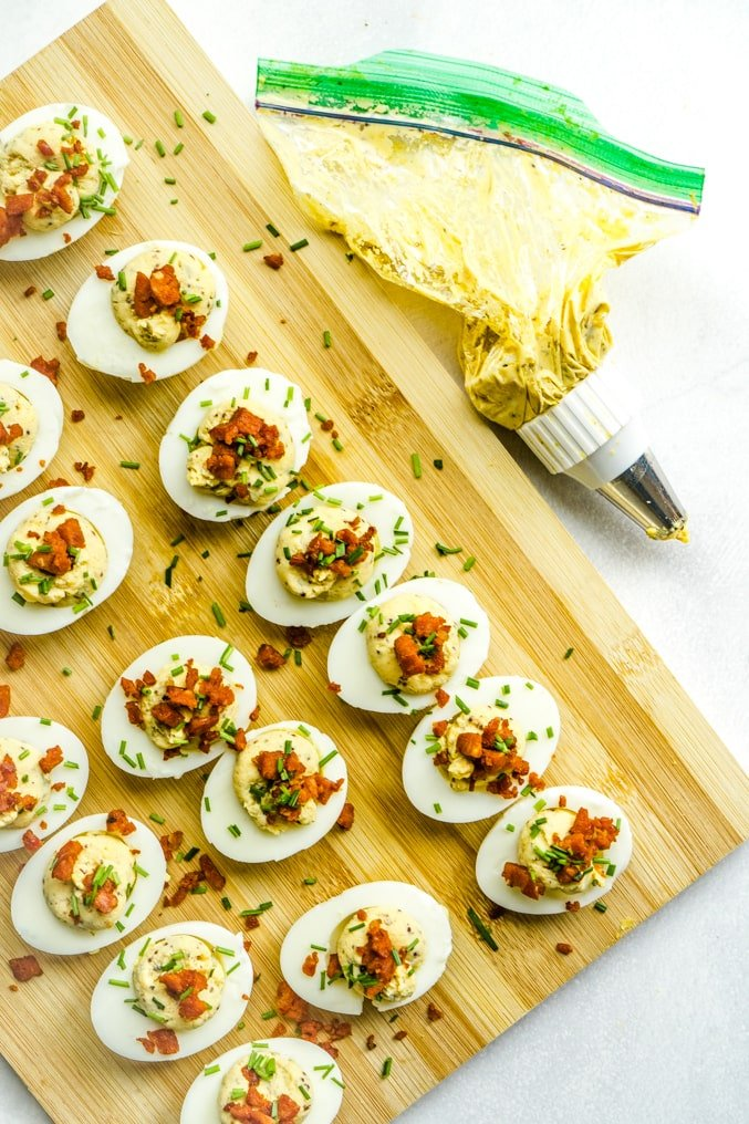 A cutting board of devilled eggs with the piping bag nearby