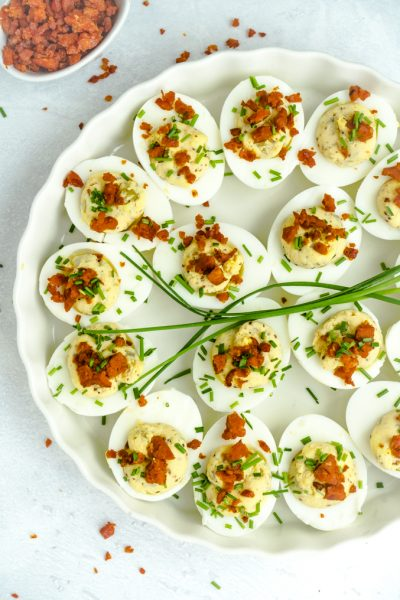 A round plate of devilled eggs topped with fresh chives and chorizo