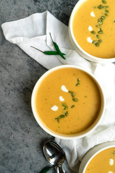 Bowls of Thai pumpkin soup on a table with a white napkin and Thai green chilis