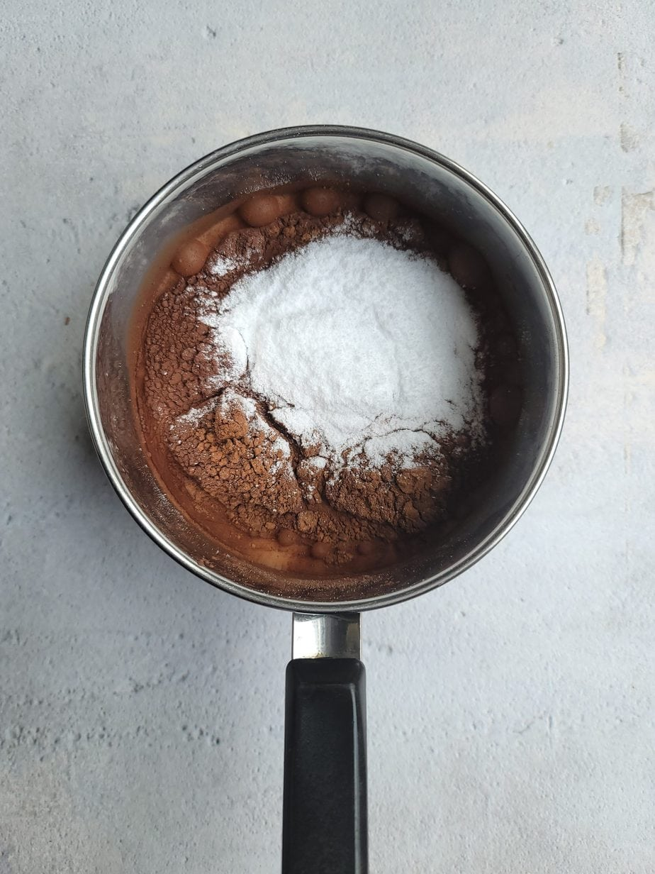 A pot filled with cocoa powder, milk and stevia