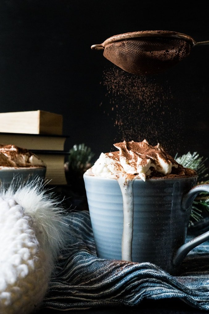 A mug of keto hot chocolate topped with sugar-free whipped cream being dusted with chocolate.